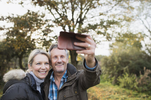 Happy mature couple taking selfie with camera phone in autumn woods - HOXF03730