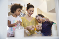 Mother and children baking in kitchen - HOXF03763