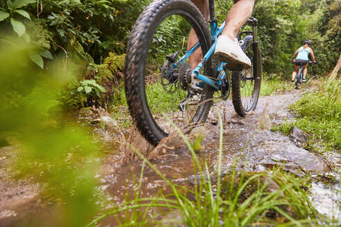 Man mountain biking, riding through puddle in woods - CAIF21315