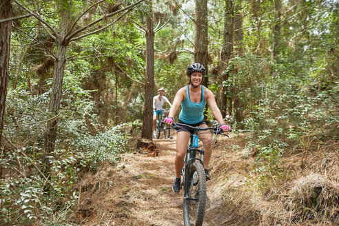 Carefree woman mountain biking on trail in woods - CAIF21318