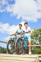 Father and son mountain biking at obstacle course - CAIF21333