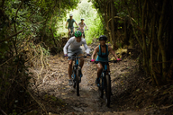 Friends mountain biking on trail in woods - CAIF21345