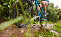 Woman mountain biking on muddy trail - CAIF21351