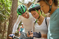 Friends mountain biking, checking wearable camera - CAIF21354