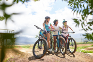 Women friends mountain biking on sunny obstacle course trail - CAIF21366