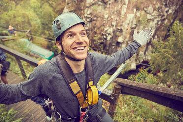 Portrait smiling, carefree man preparing to zip line - CAIF21405