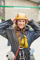 Portrait smiling young woman preparing to zip line - CAIF21408