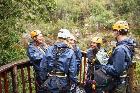Friends talking, waiting to zip line in woods - CAIF21423