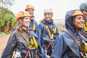 Smiling friends preparing to zip line - CAIF21429