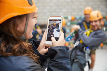 Woman with camera phone photographing friends in zip line equipment - CAIF21432