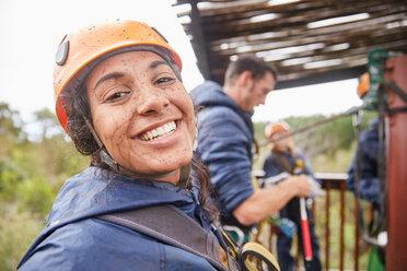 Portrait enthusiastic, muddy young woman enjoying zip lining - CAIF21438