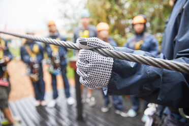Woman in glove holding zip line - CAIF21441