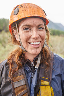 Portrait smiling, muddy woman zip lining - CAIF21444