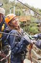 Portrait smiling, confident woman preparing to zip line - CAIF21447
