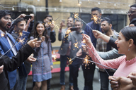 Friends celebrating with sparklers at party - CAIF21471