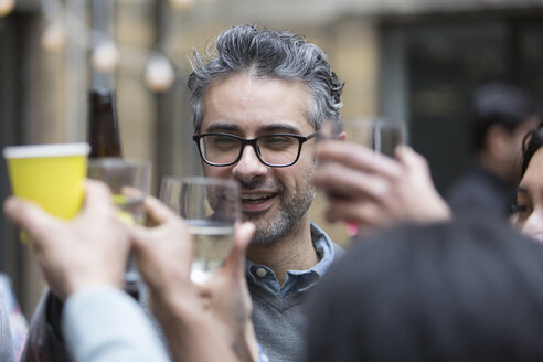 Happy man toasting drinks with friends at party - CAIF21474