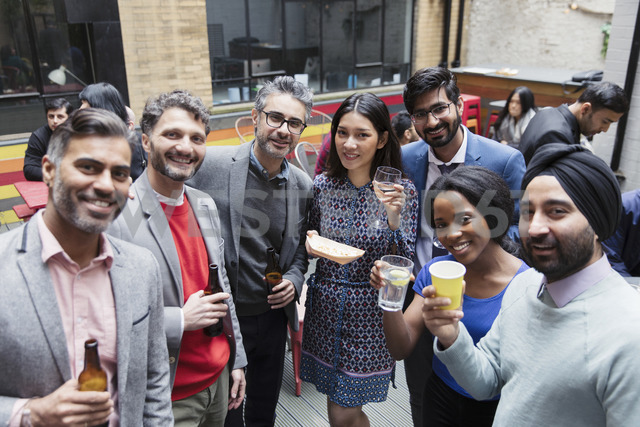 Portrait smiling friends drinking at party on patio - CAIF21477