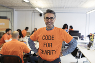 Portrait confident hacker coding for charity at hackathon - CAIF21483