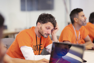 Focused hacker coding for charity at hackathon - CAIF21495