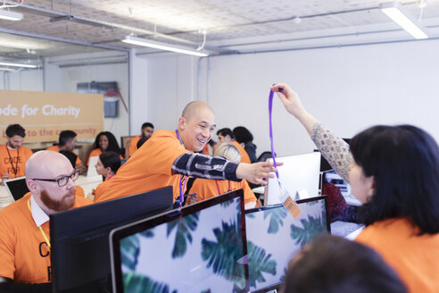 Hackers with lanyard, coding for charity at hackathon - CAIF21498