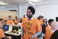 Happy, confident hacker in turban coding for charity at hackathon - CAIF21516