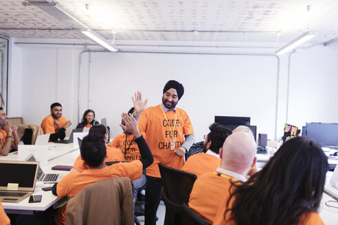 Hackers celebrating, high-fiving and coding for charity at hackathon - CAIF21519