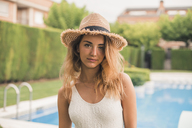 Portrait of young woman with straw hat and swimsuit, pool in the background - ACPF00266