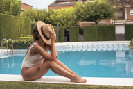 Portrait of an unrecognizable girl sitting in the pool with a straw hat on her face - ACPF00269