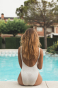 Young woman sitting at poolside, rear view - ACPF00272