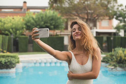 Portrait of young woman in a swimsuit making a selfie with the pool in the background - ACPF00281
