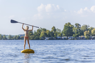 Young girl stand up paddle surfing holding paddle - TCF05661