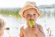 Baby boy eating melon at lake - TCF05673