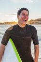 Laughing male surfer with surfboard on beach - CAIF21612