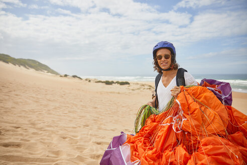 Portrait smiling male paraglider with parachute on beach - CAIF21693