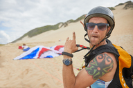 Portrait confident, carefree male paraglider on beach - CAIF21696