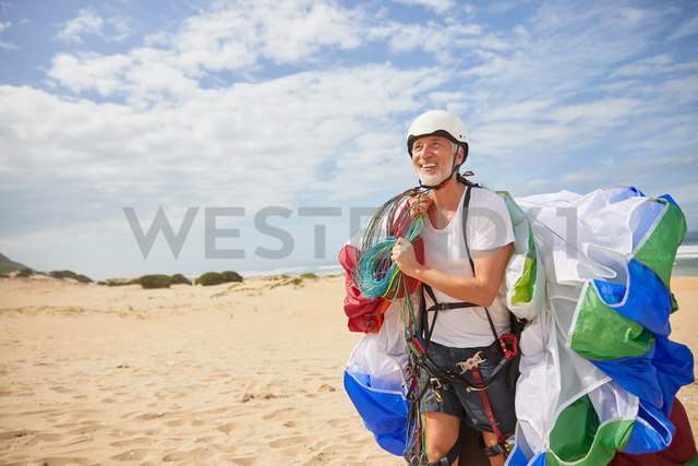 Smiling male paraglider carrying equipment and parachute on sunny beach - CAIF21705 - Trevor Adeline/Westend61