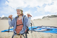 Smiling, confident paraglider with parachute on beach - CAIF21717