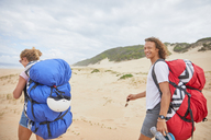 Portrait happy male paraglider with parachute backpack on beach - CAIF21720