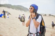 Male paraglider fastening helmet on beach - CAIF21726