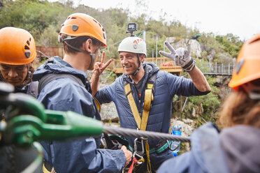 Enthusiastic man preparing to zip line, gesturing peace sign - CAIF21732
