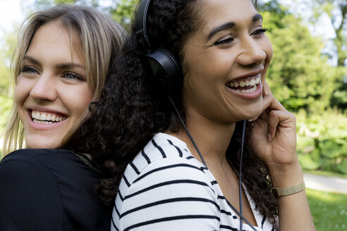 Two girlfriends in a park listening music, laughing, having fun - HHLMF00318