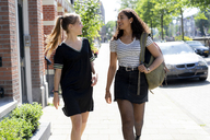Two laughing girlfriends walking in the city - HHLMF00345