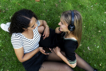 Two girlfriends in a park listening music, using smartphone - HHLMF00351