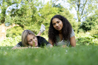 Two girlfriends relaxing in grass in a park - HHLMF00354