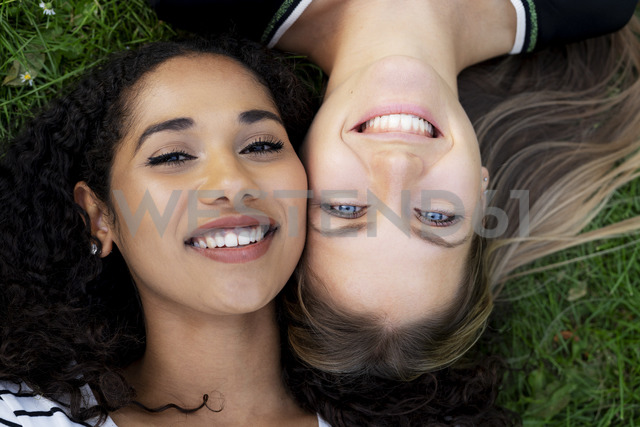 Two girlfriends relaxing in a park, lying on grass - HHLMF00357