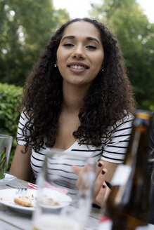 Young woman sitting in beer garden - HHLMF00360