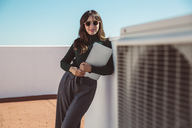 Businesswoman with sunglasses standing on rooftop, holding laptop - SUF00544