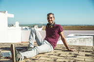Smiling man sitting on roof, enjoying summer - SUF00547