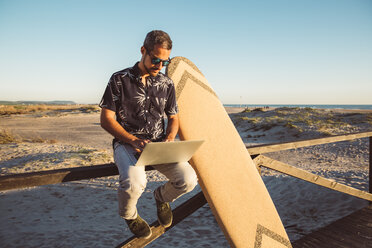 Man sitting at the beach, using laptop, with surfboard leaning on fence - SUF00562