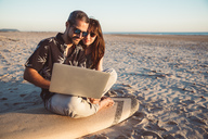 Couple with surfboard sitting on the beach, using laptop - SUF00565